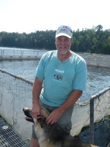 Mike Meeker and his dog Rosco stand on the dock of his rainbow trout fish farm near Evansville on Manitoulin Island.